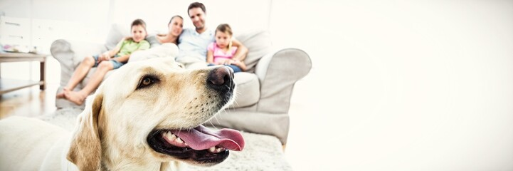 Happy family sitting on couch with their pet yellow labrador in