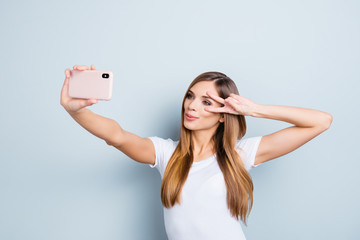 Portrait of positive cheerful girl having smart phone in hand shooting selfie on front camera gesturing v-sign near eye isolated on grey background