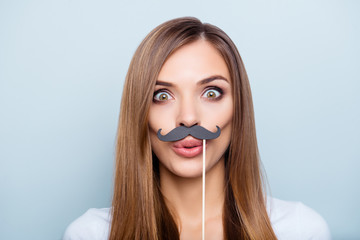 Close up portrait of funny foolish girl holding black carton mustache on stick with pout lips wide open eyes looking at camera isolated on grey background