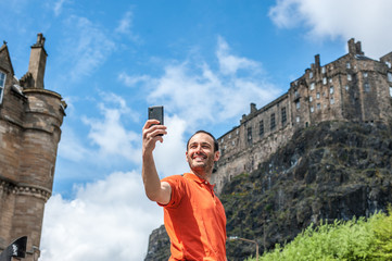 A happy young man tourist taking selfie at Edinburgh Castle with mobile phone.