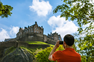 A man tourist taking picture of Edinburgh Castle in spring time on mobile phone.