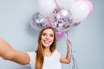 Self portrait of creative positive girl in casual outfit having pink and white air balloons in hand shooting selfie on front camera isolated on grey background