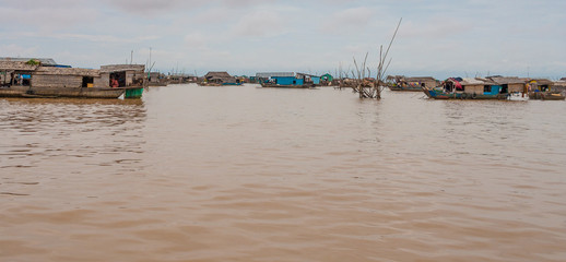 Surrounded by several wooden houseboats in the center of the floating village Chong Kneas on Tonle Sap Lake in Cambodia.