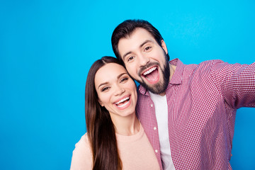 Self portrait of toothy lucky partners with beaming smiles shooting selfie on front camera isolated on vivid blue background
