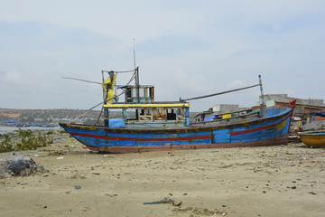 An old abandoned fishing boat in Mui Ne Fishing Village, Binh Thuan Province, Vietnam