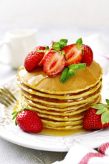Stack of delicious pancakes with maple syrup and fresh strawberry for a breakfast.