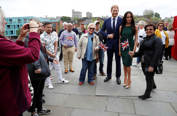 People pose for pictures with models of Britain's Prince Harry and Meghan Markle ahead of their wedding, in Windsor