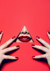 Red lips look through the hole in the red paper. Fingers in the face with bright red manicure.