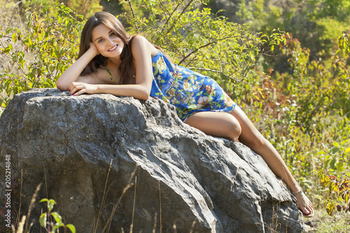 751ebe0e6ce Young woman brunette lying on the rock. Shines the bright sun. She is  wearing a blue summer dress.