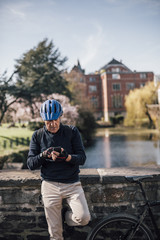 Senior man with cycling helmet using smartphone