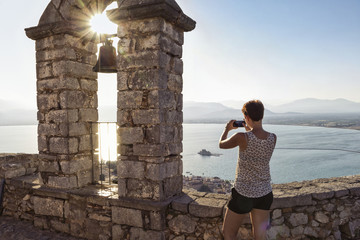 Greece, Peloponnese, Argolis, Nauplia, Argolic Gulf, woman photographing view from bell tower of Palamidi Fortress