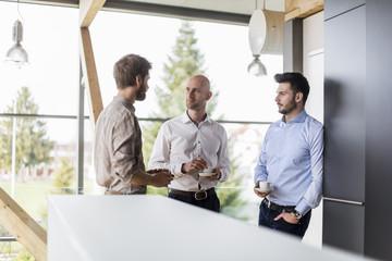 Three businessmen talking during coffee break