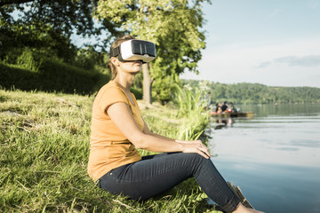 Woman sitting at a lake wearing VR glasses