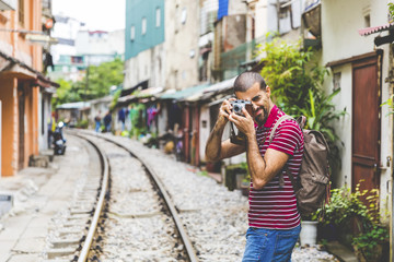 Vietnam, Hanoi, man in the city taking a picture with an old-fashioned camera