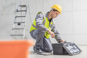 Construction worker with tool box on construction site