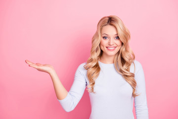 Portrait of nice student, foolish freelancer, good wife, friendly girl with curls modern hairdo looking at camera isolated on pink background holding copy space empty place on her palm