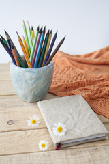 Wooden bright pencils, orange plaid, three flowers of chamomile and a glass of handmade on a wooden background.
