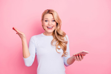 OMG! Portrait of astonished student, glad girlfriend having smart phone cellphone in hand looking at camera gesturing with palm isolated on pink background