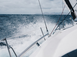 Left side deck view of a small luxury yacht sailing in an open sea during the day. Big splashes. Sailing boat going in the ocean