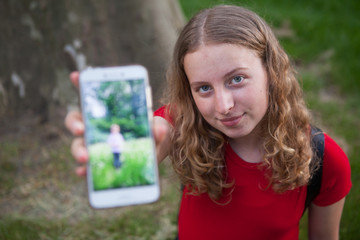 Girl showing a picture taken of her little brother on her mobile phone