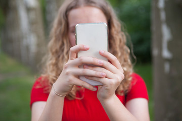 Girl taking a selfie with a mobile phone or writing something.