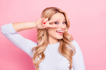 Wall Mural - Hey! Portrait of carefree friendly  girl with modern hairdo gesturing v-sign near eye looking at camera isolated on pink background