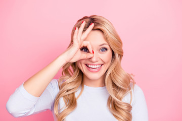 Wall Mural - Portrait of cheerful freelancer, creative girlfriend, toothy student, foolish girl gesturing ok sign with fingers near one eye isolated on pink background