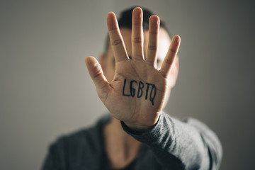 man with the text LGBTQ in his hand