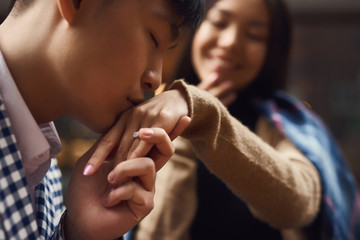 Guy kisses hand of girl sitting at table in cafe.