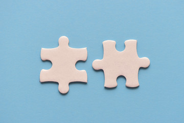 Wall Mural - Two white details of puzzle on blue background