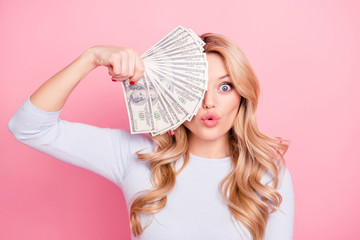 Portrait of playful foolish girl with curls, modern hairstyle, pout lips hiding half of her face with fan of much money isolated on pink background