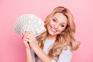 Portrait of charming pretty girl in casual outfit holding fan of a lot of money for shopping in hands looking at camera, isolated on pink background