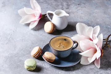 Blue cup of black espresso coffee with french dessert macaroons, cream and spring flowers magnolia branches over grey texture background. Top view, space.