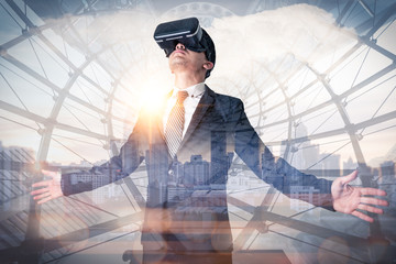 The double exposure image of the business man using a VR glasses during sunrise overlay with cityscape image. the concept of business, communication, gaming, internet of things and future life.