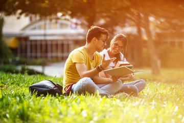 Two young students sitting at the campus yard , reading book and preparing for university exam.
