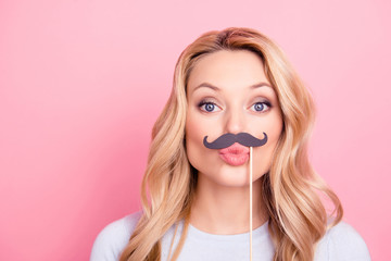 Portrait of funky flirting girl with black carton mustache on stick sending blowing kiss with pout lips to the camera isolated on pink background