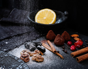 Truffles in cocoa powder, cinnamon sticks, nuts and dried fruits on a black background