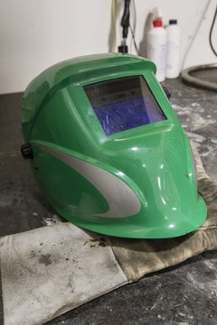 Green welding hood and leather gloves.