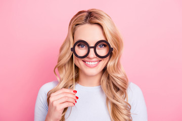 Portrait of  foolish positive girlfriend having black carton glasses on stick in hand looking at camera isolated on pink background. Accessory concept