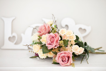 A bouquet of delicate flowers with an inscription LOVE on a white background