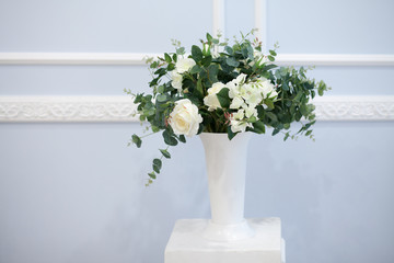 Bouquet of delicate flowers in a white vase on a blue background