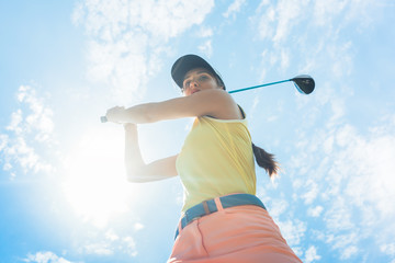 Low-angle view of a female professional player holding up the iron club with concentration for strike while playing golf outdoors against cloudy sky