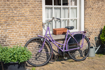 Purple ladies bike against a brick wall