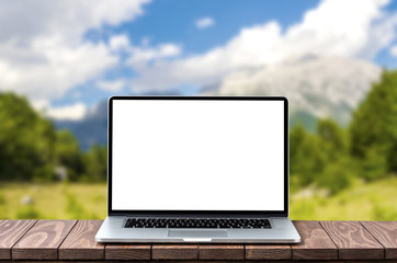 Modern laptop with empty white screen on wooden table against blurred mountains background