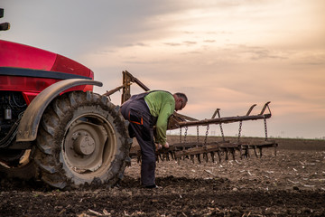 Wall Mural - Farmer in tractor preparing land with seedbed cultivator as part of pre seeding activities in early spring season of agricultural works at farmlands.