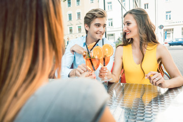 Young happy couple toasting with fresh orange cocktails with their mutual female friend at a trendy restaurant downtown