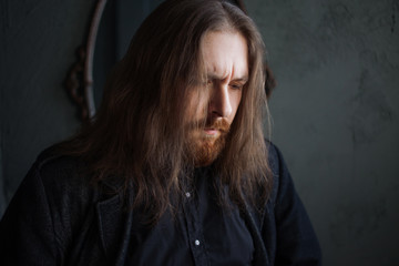 Portrait of man with long hair and beard in black clothes on dark background