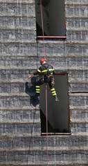 climber of firefighter climbing a wall of a house
