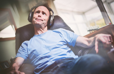 The older generation being driven crazy listening to modern youthful music on wireless headphones. Styling and grain effect added to image.