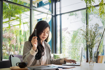 young businesswoman working with mobile laptop and documents in office, business concept